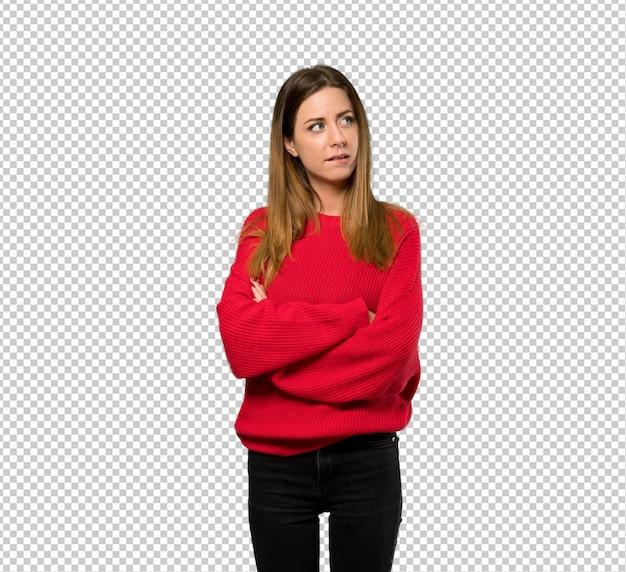 唇に刺されながら混乱の表情で赤いセーターを持つ若い女