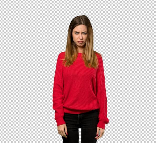 悲しいと落ち込んで表情で赤いセーターを持つ若い女