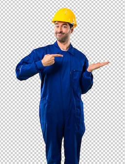 Young workman with helmet holding copyspace imaginary on the palm to insert an ad