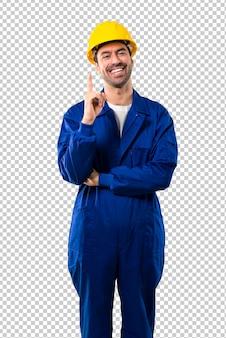 Молодой работник с шлемом, показывая и поднимая палец в знак лучших