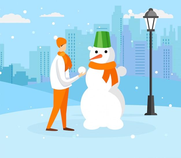 雪だるまを作る暖かい冬服で10代の少年