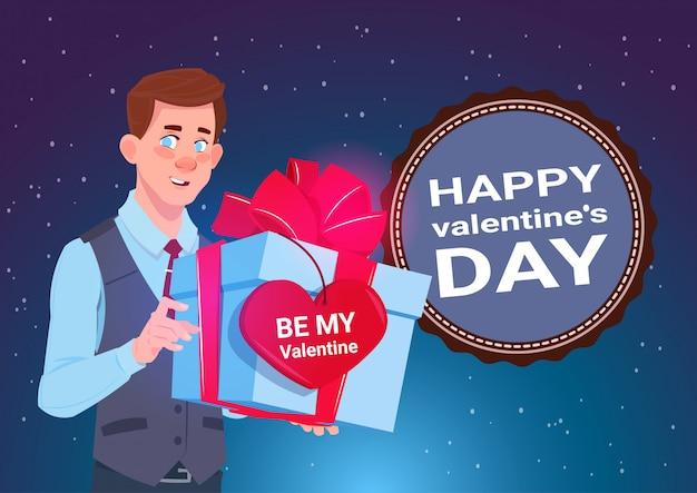 バレンタインデーコンセプトバナーハート形のラベルが付いたギフトボックスを持ったかわいい男2月14日ホリデー