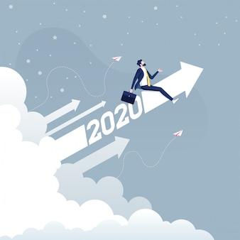 ビジネスコンセプトに上がって2020矢印に乗るビジネスマン