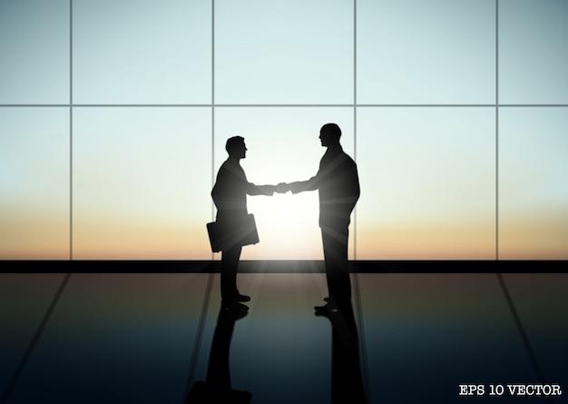 2人のビジネスマンが握手しています。