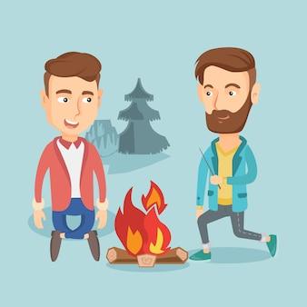 キャンプでき火の周りに座っている2人の友人。