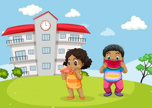 2人の子供が学校の正面で食べる