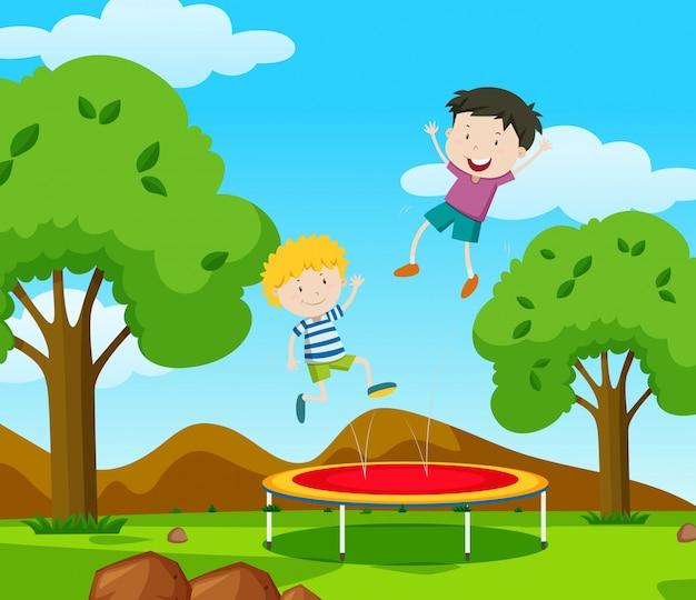 2人の男の子が公園のトランポリンで跳ね返っている