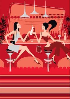 2人の美しい女の子がナイトクラブでカクテルを飲みます。