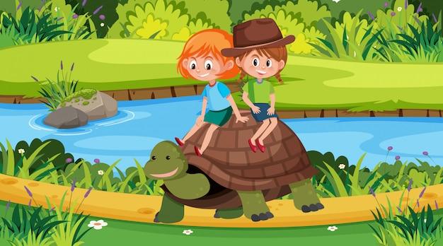 公園でカメに乗っている2人の女の子とのシーン