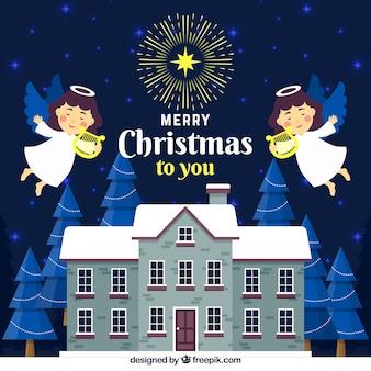2つのクリスマスの天使が家の上を飛んで