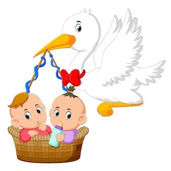 コウノトリはその中に2人の赤ちゃんと一緒にバスケットを持っています。