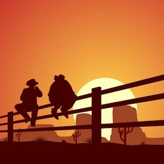 2つのカウボーイのシルエットは木製のフェンスに座っていた