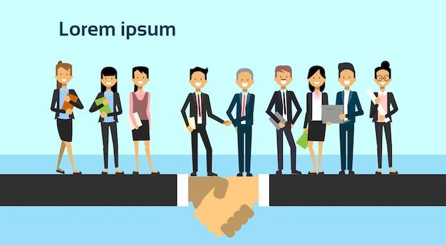 ビジネスマンの合意とパートナーシップの概念のグループの上に握手2人のビジネス男性チームリーダー