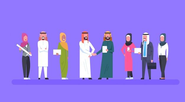 イスラム教徒のビジネスの人々のチーム上の2つのアラブのビジネスマンリーダーハンドシェイクパートナーシップと契約の概念