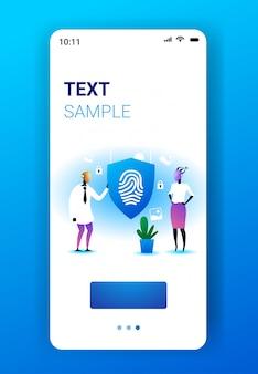 指紋ガード付きシールドを保持している2つのロボットプライバシーデータ保護セキュリティ人工知能技術コンセプトモバイルアプリスマートフォン画面垂直全長コピースペース