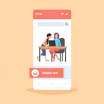 ビジネスウーマンの同僚が職場の机に座って2人のビジネス女性がラップトップの作業プロセスチームワークの概念を使用してスマートフォンの画面モバイルアプリの全長