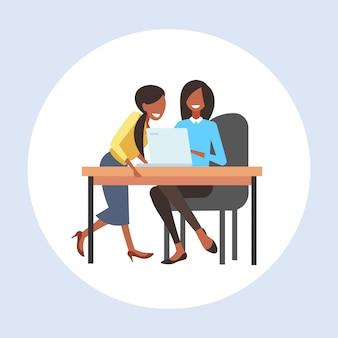 ラップトップ作業プロセスチームワークコンセプト全長を使用して、職場の机に座っているビジネスウーマンの同僚2人のビジネス女性