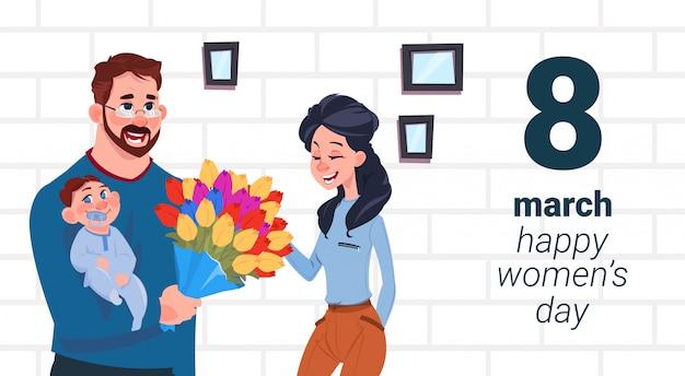 赤ちゃんの挨拶を持つ父幸せな女性の日クリエイティブカードを持つ母3月8日休日の概念