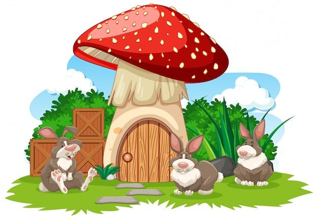 白い背景の上の3つのウサギの漫画のスタイルでキノコの家