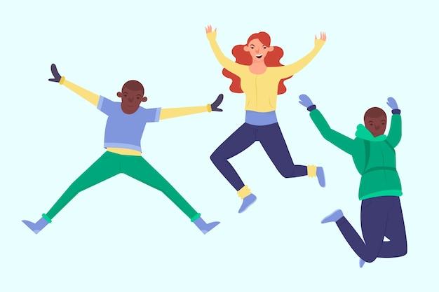 ジャンプする冬の服を着ている3人の若者