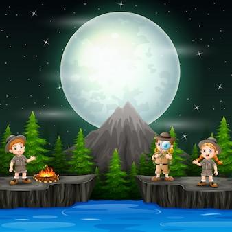 夜のシーンでキャンプファイヤーを持つ3人の探検家の子供たち