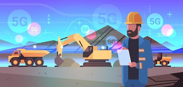 オープンピットの男性労働者タブレット5 gオンラインワイヤレスシステム接続掘削機を使用して掘削機の土をダンプトラックの炭鉱の生産露天掘りの石の採石場の背景の肖像画の水平方向に読み込み