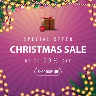 特別オファー、クリスマスセール、最大50%オフ。クリスマスツリーの枝と花輪のピンクの割引バナー。