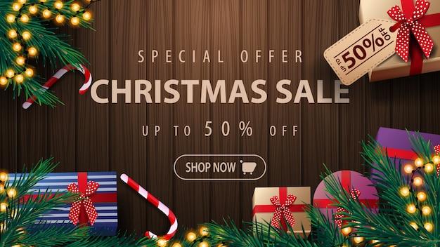 Специальное предложение, новогодняя распродажа, скидка до 50%, баннер со скидкой на деревянном фоне, гирлянда, ветки елки, подарки и леденцы, вид сверху