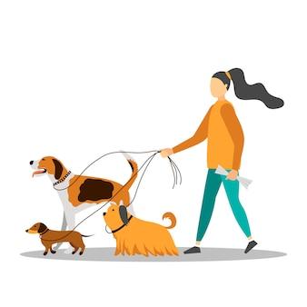 5匹の犬と一緒に歩いている若い女性。