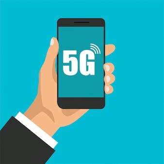 高速5gテクノロジーを搭載したスマートフォン。手は、ディスプレイ上のインターネット信号記号で携帯電話を保持しています。