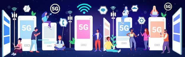 Смешайте расы людей, использующих приложения на цифровых устройствах 5g онлайн беспроводные системы связи концепция социальной сети связи