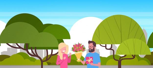 Человек подарил девушке подарок и цветы к международному женскому дню 8 марта на свежем воздухе в парке
