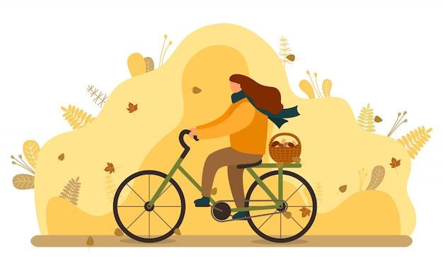 秋のキノコのバスケットを持つ女性に乗る自転車