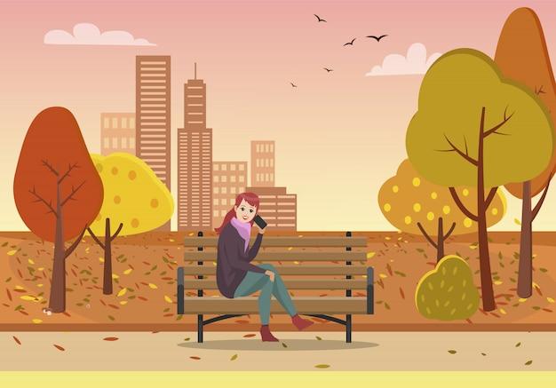 Осенний парк и женщина разговаривают по телефону на скамейке