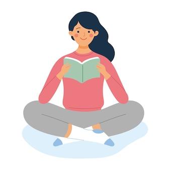 Молодая девушка сидит и читает книгу,