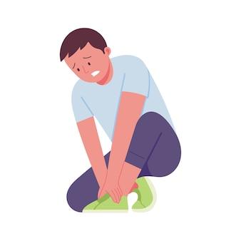 怪我のために足を抱えている痛みの表情を持つ若い男