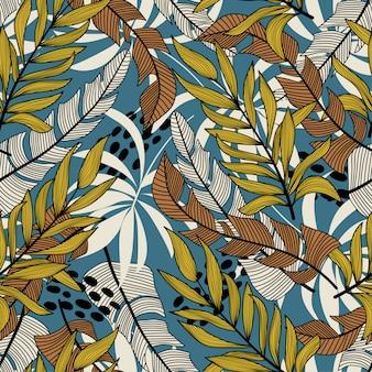 Абстрактная тенденция бесшовные модели с разноцветными тропическими листьями и растениями на синем фоне