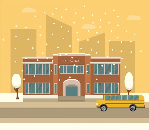 高校の建物。黄色のスクールバス。雪が降っている冬の街の風景。