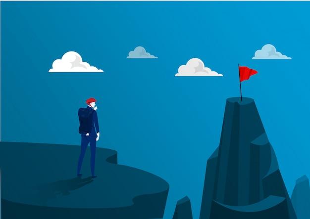 山の冒険の上に立っているビジネスは赤い旗をゴールに行く