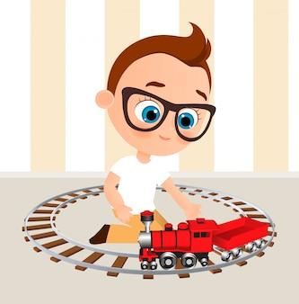 メガネとおもちゃの電車を持つ少年。電車で遊ぶ少年。
