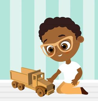 メガネとおもちゃの車を持つアフリカ系アメリカ人の少年。車をしている少年。