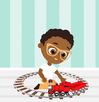 メガネとおもちゃの列車のアフリカ系アメリカ人の少年。電車で遊ぶ少年