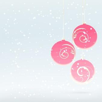 ピンクのクリスマスボールと雪に覆われた背景