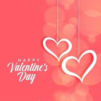 バレンタインデーの背景のピンクのボケ味にぶら下がっている心