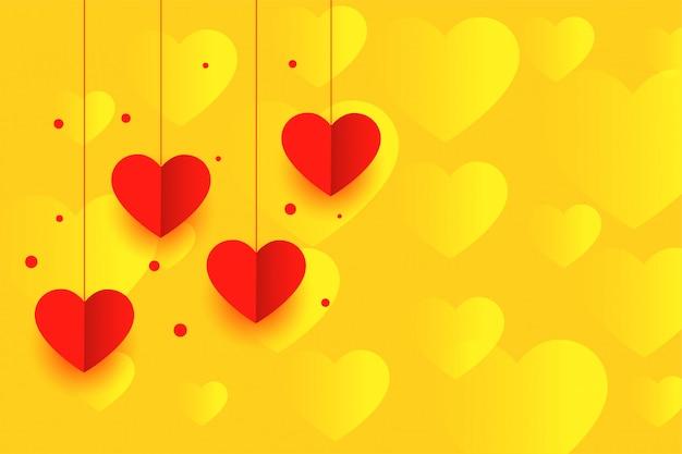Желтый фон с красным висящими бумажными сердечками