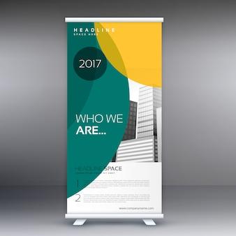 現代の立ち見客は、ビジネスプレゼンテーションのための緑と黄色の形状のバナーデザインをロールアップ