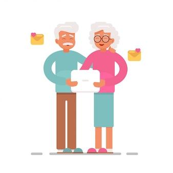 年配のカップルがラップトップコンピューターで電子メールを送受信します。