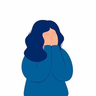 彼女の手で彼女の顔を覆って泣いて落ち込んでいる若い女の子