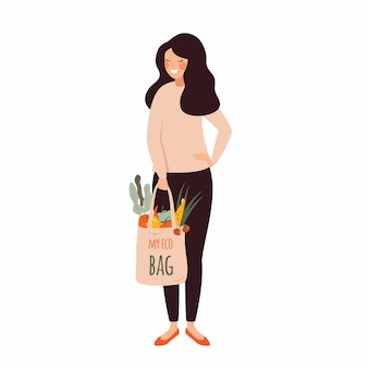 若い女性は彼女の手で新鮮な野菜でいっぱいエココットンバッグを保持します。