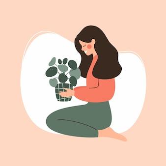 若い女の子は鉢植えの緑の植物を保持します